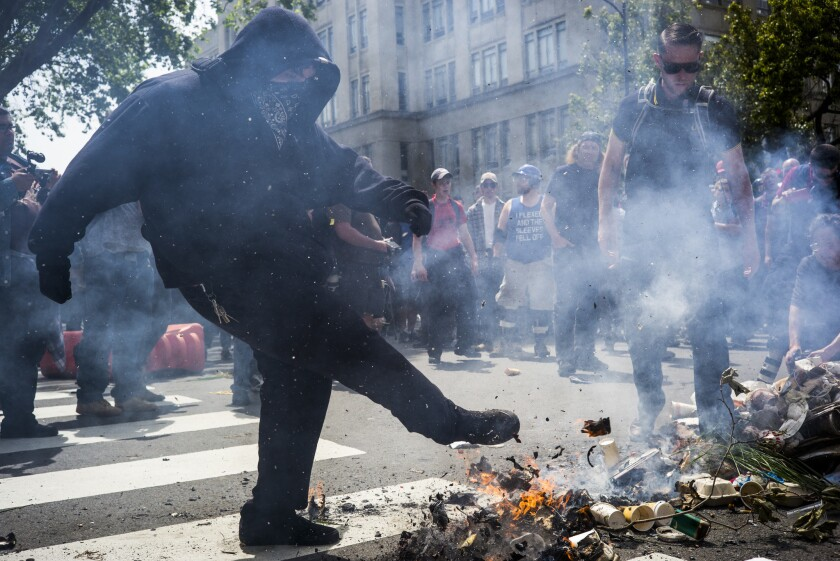 A protester kicks trash removed from a can and set on fire during a pro-Trump rally Saturday in