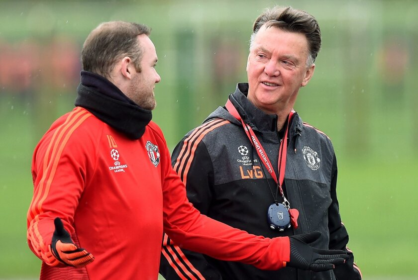 Manchester United manager Louis van Gaal, right, talks with Wayne Rooney during a training session at the team's training complex in Manchester, England, Tuesday Nov. 24, 2015. United will play PSV Eindhoven in a Champions League soccer match on Wednersday. (Martin Rickett/PA via AP) UNITED KINGDOM OUT