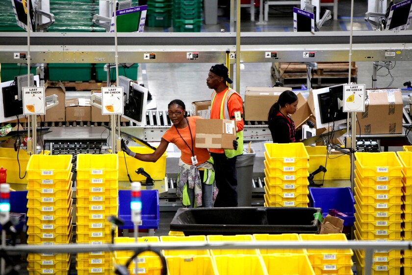 Workers in a warehouse are surrounded by yellow bins.
