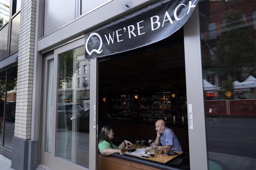 ARCHIVO - En esta foto de archivo del 4 de junio de 2021, gente cena en el restaurante Q de Portland, Oregon. Muchos estadounidenses mitigan las precauciones tomadas durante la pandemia de COVID-19 y reanudan sus actividades cotidianas, de acuerdo con una encuesta AP-NORC. (AP Foto/Paula Bronstein)