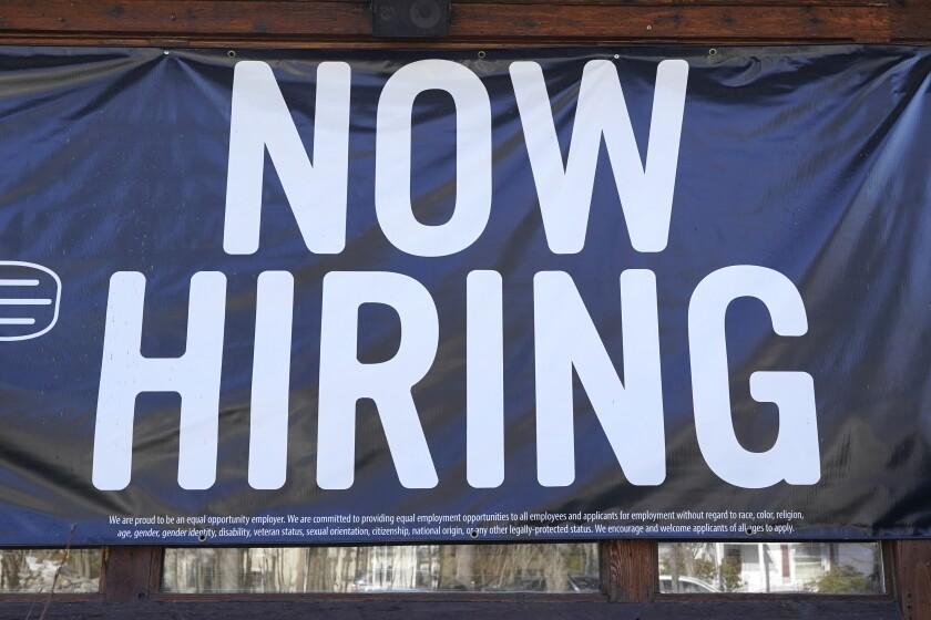 "A restaurant displays a ""Now Hiring"" sign"