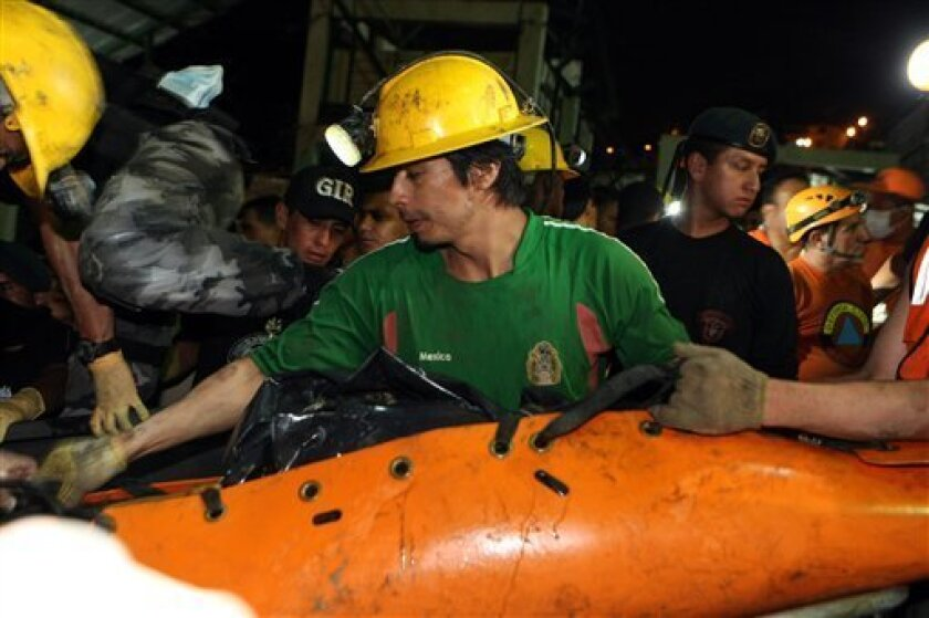 A miner loads on a truck the body of a third miner, out of four, who were found dead at the Casa Negra mine in Portovelo, Ecuador, Wednesday, Oct. 20, 2010. Search teams found the bodies of the last two missing miners Wednesday after a tunnel at the Casa Negra mine collapsed 490 feet (150 meters) u