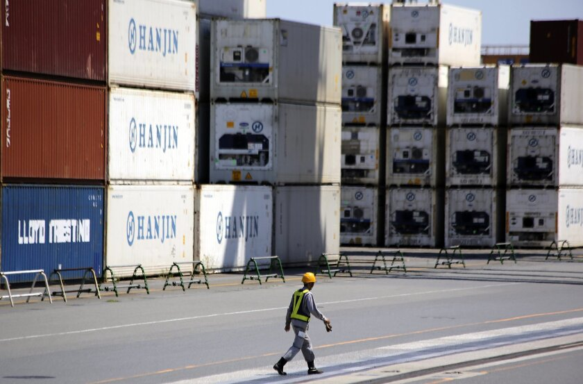 FILE - In this Aug. 20, 2014 file photo, a port worker walks past a piles of cargo at a container terminal in Tokyo. Japan's trade deficit expanded in November from the month before despite a slight decrease in imports thanks to the recent plunge in crude oil prices and Japan's return to recession.