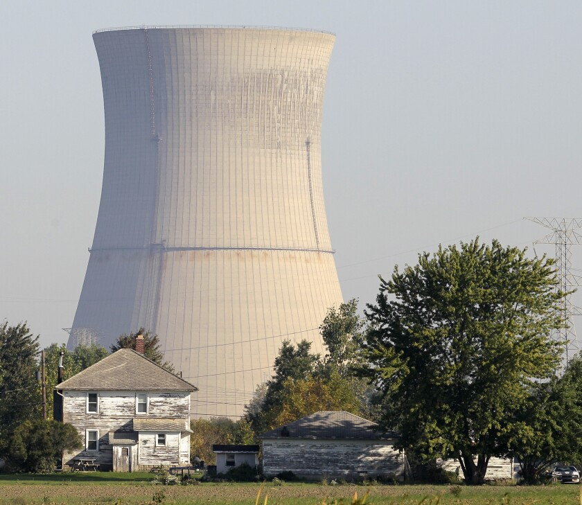 FILE-In this Oct. 5, 2011 file photo, the cooling tower of the Davis-Besse Nuclear Power Station looms over an adjacent farm in Oak Harbor, Ohio. Across the nation, a handful of nuclear plants unable to compete with natural gas and renewable energy have shut down within the last two years, taking away steady and lucrative sources of tax money for schools, roads and libraries. The uncertainty surrounding the future of both Ohio plants, Davis-Besse near Toledo and Perry near Cleveland, has created plenty of nervousness in their hometowns that have found themselves caught in the middle of the scandal-tainted bailout. (AP Photo/Amy Sancetta, File)