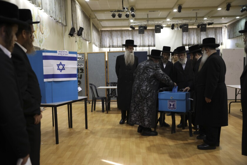 FILE - In this Tuesday, Sept. 17, 2019 file photo, ultra-Orthodox Jews watch Rabbi Israel Hager vote in Bnei Brak, Israel. In Israel's secular heartland, the role of religion in daily life played a central role in this week's deadlocked election. Prime Minister Benjamin Netanyahu's tight alliance with the ultra-Orthodox may have contributed to his second-place finish. (AP Photo/Oded Balilty, File)