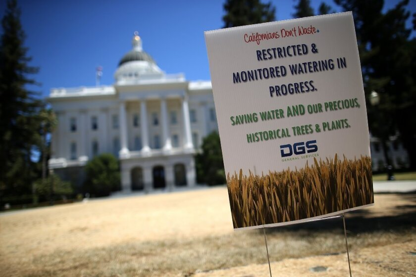 A sign explaining reduced and restricted watering is posted on the dead lawn in front of the California state Capitol in Sacramento on June 18.