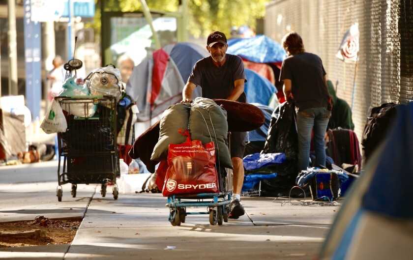 Homeless people pack up their belongings along First Street between Broadway and Spring Street during a cleanup Monday morning. The area targeted the sidewalk in front of a fenced-in empty lot next to a portion of Grand Park used for parking during scheduled events.