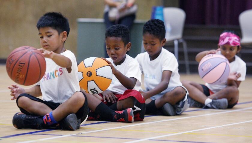 A line of four children sitting cross-legged and dribbling basketballs