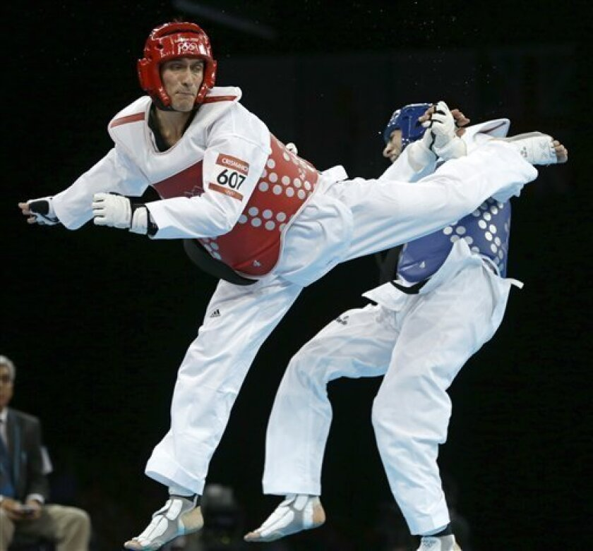 Armenia's Arman Yeremyan fights Argentina's Sebastian Eduardo Crismanich (in red) during their semifinal round match in men's 80-kg taekwondo competition at the 2012 Summer Olympics, Friday, Aug. 10, 2012, in London. (AP Photo/Ng Han Guan)