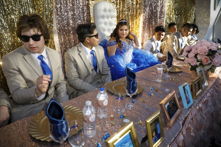 Alexis Osuna in a blue gown and her chambelanes (escorts of honor) in sun glasses celebrate her postponed quinceañera .