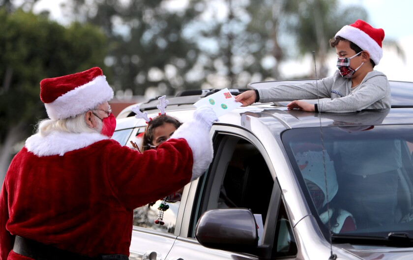 Santa Claus receives a personalized letter from 6-year-old Joey Martinez as his twin sister, Elyse, looks on.