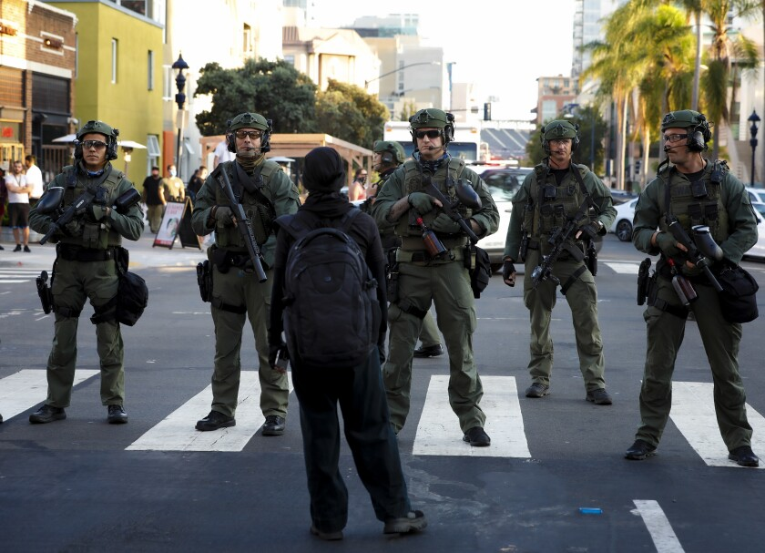 SWAT officers stand in front of a protester during a demonstration on Aug. 28.