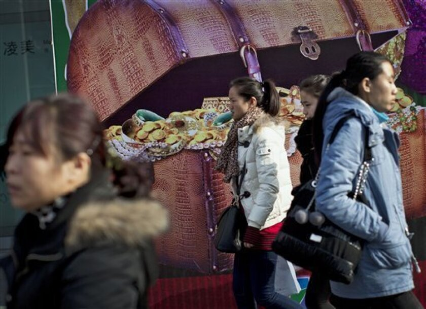 Chinese women walk past a billboard showing a box full of gold coins and jewelry, outside a shopping mall in Beijing, China, Thursday, Dec. 1, 2011. Chinese leaders are scrambling to shore up flagging economic growth as exports weaken, abruptly reversing course after they spent two years struggling to cool an overheated expansion and surging inflation. (AP Photo/Andy Wong)