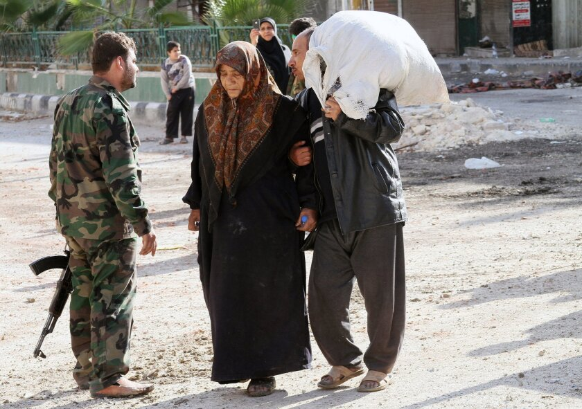 A Syrian soldier is passed by civilians carrying their belongings in the town of Hejeira in the countryside of Damascus which Syrian troops captured on Wednesday, Nov. 13, 2013 as the government forged ahead with a military offensive that already has taken four other opposition strongholds south of