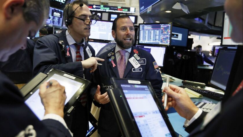 Specialist Michael Pistillo center, works with traders at his post on the floor of the New York Stock Exchange this month.