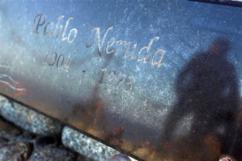 A visitor is reflected on the marble of the tomb of literature Nobel laureate Pablo Neruda in Isla Negra, Chile, Sunday April 7, 2013. The body of Neruda will be exhumed in an effort to clear up four decades of suspicion about how the poet died in the days after Chile's military coup. (AP Photo / Luis Hidalgo).