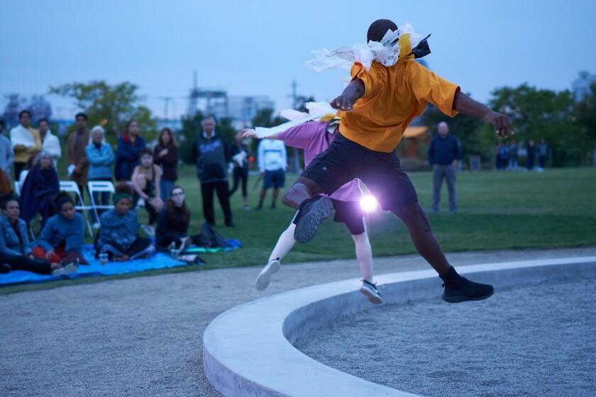 Dancers perform for spectators on a park's lawn.