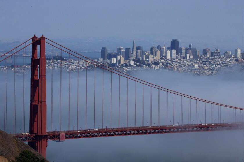 The Golden Gate Bridge and San Francisco skyline are seen amid fog.