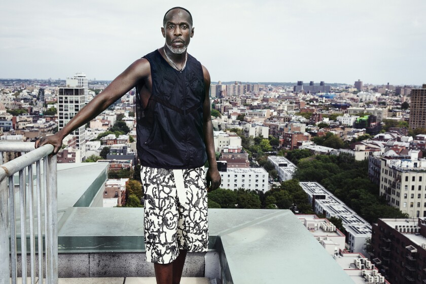 Michael K. Williams stands on a Brooklyn rooftop in black sleeveless tee and white patterned shorts.