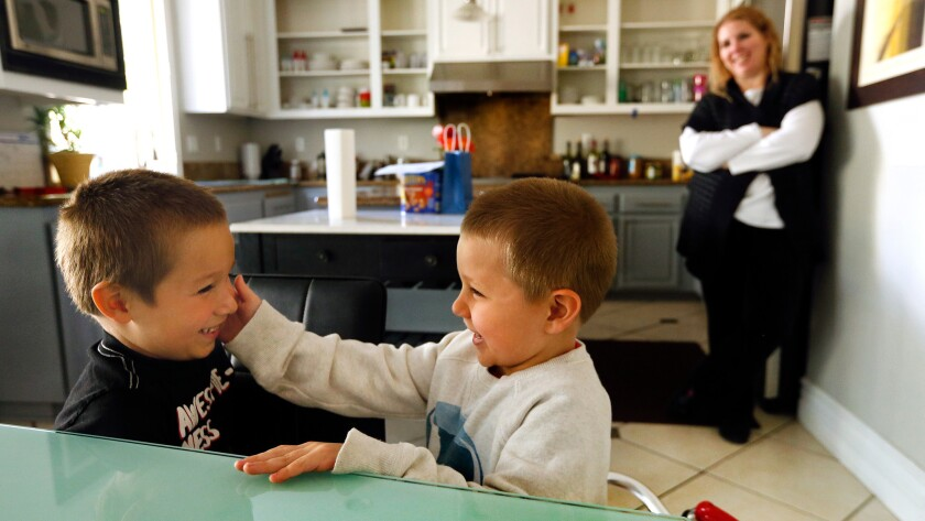 Lucian Olivera, center, touches the face of his brother, Nikolas, with his cold hand, a result of holding a bag of ice, while inside the kitchen of their home in Moorpark.