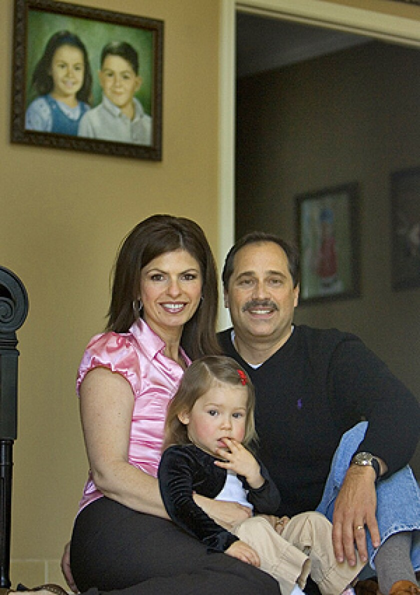 Bob and Carmen Pack play with their two-year-old daughter Noelle, in front of a painting of the couple's deceased children Troy and Alana, April 25, 2008 in Danville, California. They were killed nearly five years ago when a woman, under the influence of prescription drugs and alcohol hit them with her car while they were walking with their mother.