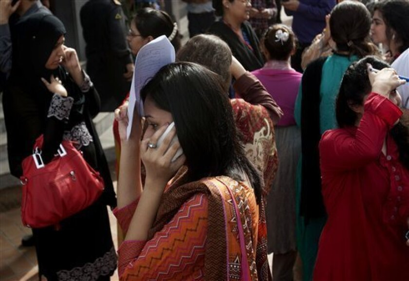 People evacuate buildings and call their relatives after a tremor of an earthquake was felt in Karachi, Pakistan, Tuesday, April 16, 2013. A major earthquake described as the strongest to hit Iran in more than half a century flatted homes and offices Tuesday near Iran's border with Pakistan, killin