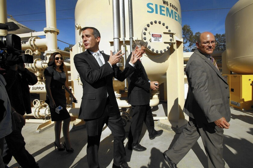 L.A. Mayor Eric Garcetti, center, walks with Department of Water and Power officials at an Arleta fa