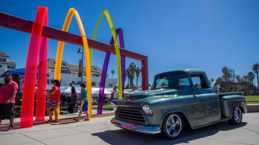 A classic Chevy pickup sits parked by the Imperial Beach sign.