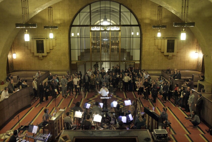 """The orchestra conducts a dress rehearsal of the opera """"Invisible Cities"""" in Union Station in Los Angeles on Oct. 17, 2013. The performance of The Industry company's new opera, based on Italo Calvino's novel with music by composer Christopher Cerrone, uses remote audio devices that allow performers and audience members wearing headsets to mingle among the train passengers and experience the opera environmentally."""