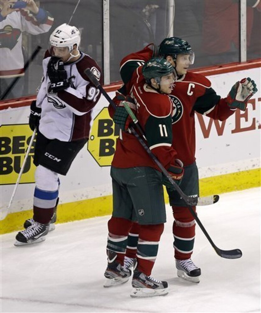 Minnesota Wild's Zach Parise, front left, and Mikko Koivu of Finland, celebrate Koivu's empty-net goal as Colorado Avalanche's Gabriel Landeskog, of Sweden, skates behind them late in the third period of an NHL hockey game Thursday, March 14, 2013, in St. Paul, Minn. The Wild won 5-3. Koivu also sc