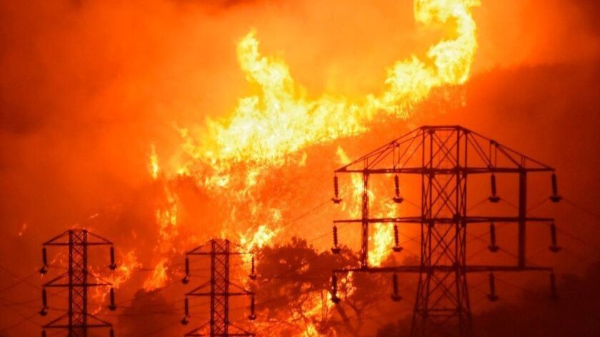 Flames burn near power lines in Montecito, Calif., in December 2017.