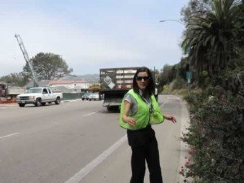 On Aug. 10, Sherry Nooravi walks in the bike lane on Torrey Pines Road, just west of Amalfi Street, where no sidewalk exists. Shelli DeRobertis photos