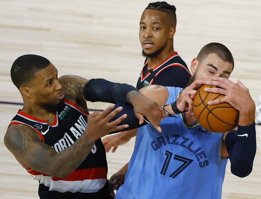The Memphis Grizzlies' Jonas Valanciunas and Portland Trail Blazers' Damian Lillard tangle.