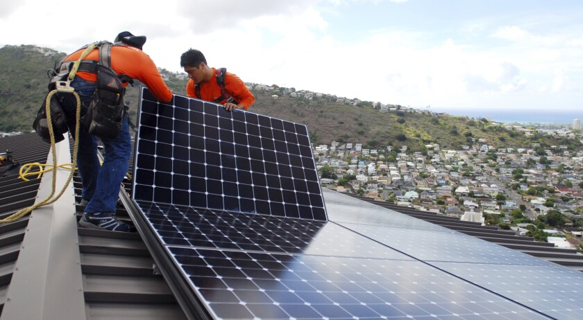 FILE - In this July 8, 2016, file photo, Radford Takashima, left, installer for RevoluSun, and lead installer Dane Hew Len, right, place solar panels on a roof in Honolulu. If you have the cash, most experts agree buying a solar system outright is a better investment than leasing or taking out a loan. Customers should check electric bills to estimate monthly energy use when deciding what size system to buy, and calculate federal or state incentives. (AP Photo/Cathy Bussewitz, File)