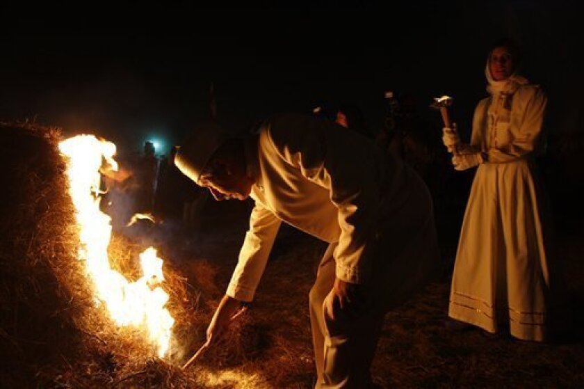 An Iranian Zoroastrian priest sets fire to a prepared pile of wood, where Zoroastrians gather in a ceremony to mark Sadeh, an ancient feast celebrating the creation of fire, outside the capital of Tehran, Iran, Saturday, Jan. 30, 2010. Some thousands of Iranians gathered at dusk to light giant bonfires in an ancient mid-winter festival dating back to Iran's pre-Islamic past that is provoking new interest among Muslims. (AP Photo/Vahid Salemi)