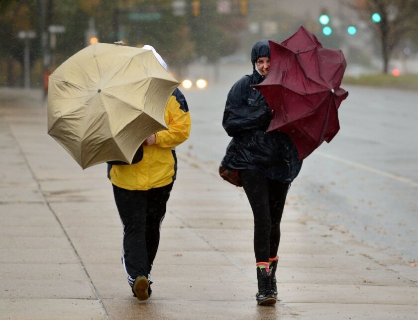 Two women make their way through the rain Monday in Philadelphia. The city was counting itself lucky, despite widespread power outages, as the effects of the storm were not devastating.