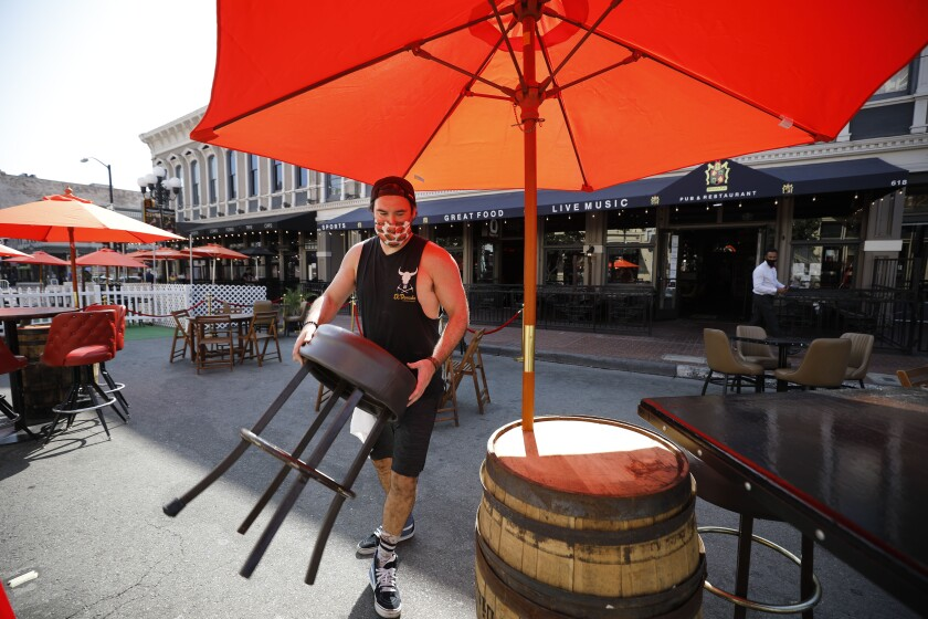 Bob McCarthy sets out seating for Henry's Pub & Restaurant on 5th Ave. in the Gaslamp Quarter.