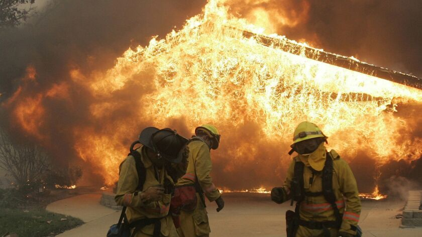 FILE - In this Oct. 22, 2007 file photo, three firefighters brace themselves from explosive heat com