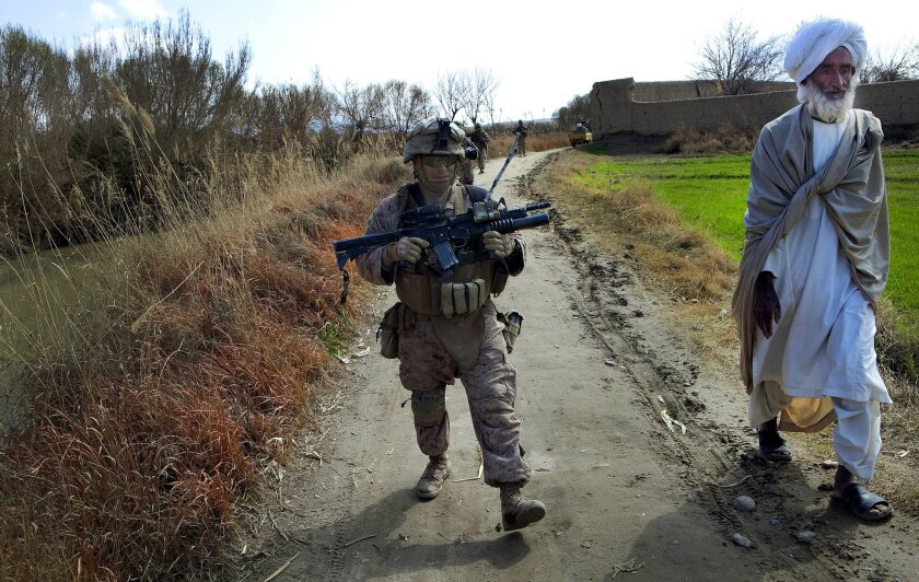 Sgt. Nat Silva from Lima Company continues his patrol after an Afghan religious leader (right) pointed out a hidden IED to the Marines.