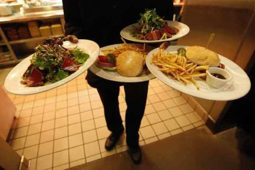 A Los Angeles waiter prepares to deliver lunch. A new report found that such workers often go without sick pay, promotions or healthcare.