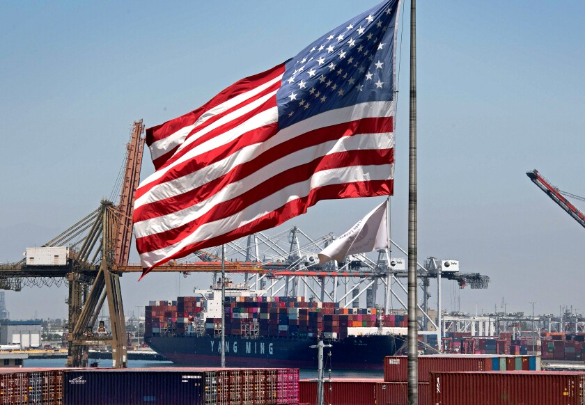 U.S. flag flies over a container ship in the Port of Long Beach