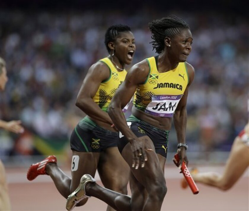 Jamaica's Kerron Stewart gets the baton from her teammate Schillonie Calvert, left, in a women's 4x100-meter relay heat at the athletics in the Olympic Stadium at the 2012 Summer Olympics, London, Thursday, Aug. 9, 2012. (AP Photo/Matt Slocum)