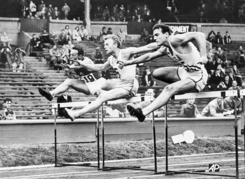 FILE - In this Aug. 7. 1948 file photo, Bob Mathias, right, is shown during the Olympic decathlon in London. At left is Oto Rebula of Yugoslavia and at center is Orn Clausen of Iceland. The Associated Press was in London when it staged the first Olympics after World War II. Bob Mathias took up decathlon at the suggestion of his high school coach in Tulare, California. Less than three months later he qualified for the 1948 Games and soon found himself standing in Wembley Stadium. Mathias won the decathlon and, at 17, became the youngest male winner of a track and field event in Olympic history. (AP Photo, File)