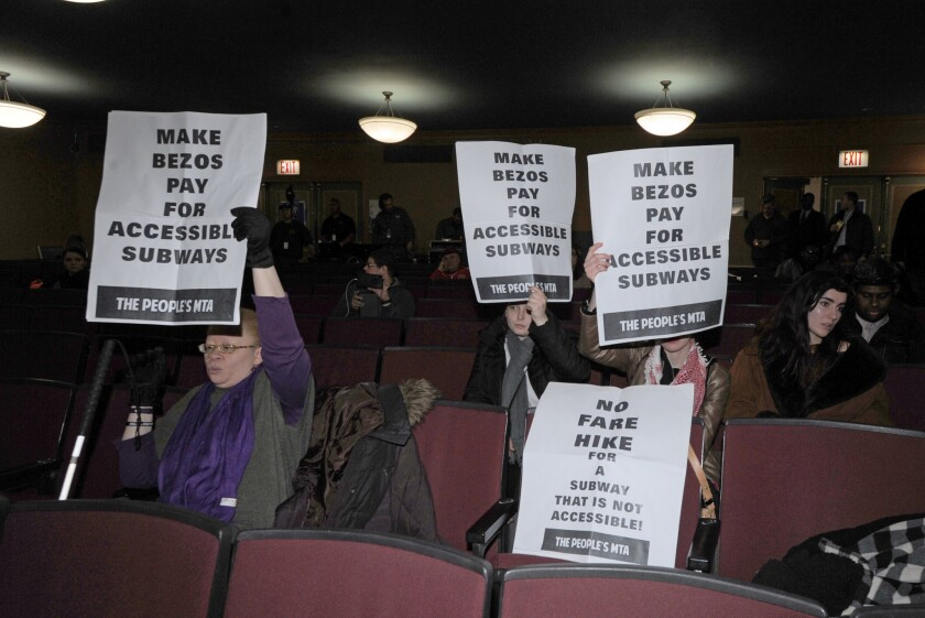 Protesters hold signs during a meeting of the Metropolitan Transportation Authority at Baruch College in Manhattan Tuesday on fare and toll hikes that would take effect in March, if approved.