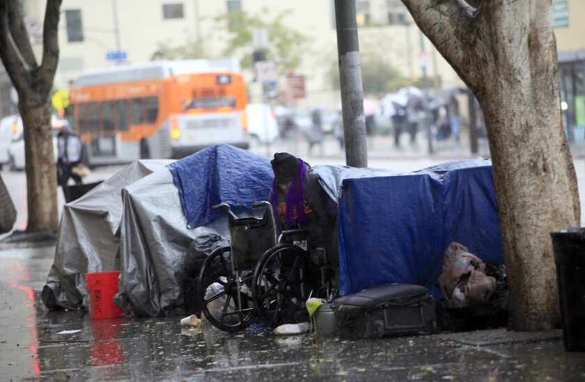 A woman emerges from her tent outside the Union Rescue Mission on skid row in Los Angeles.