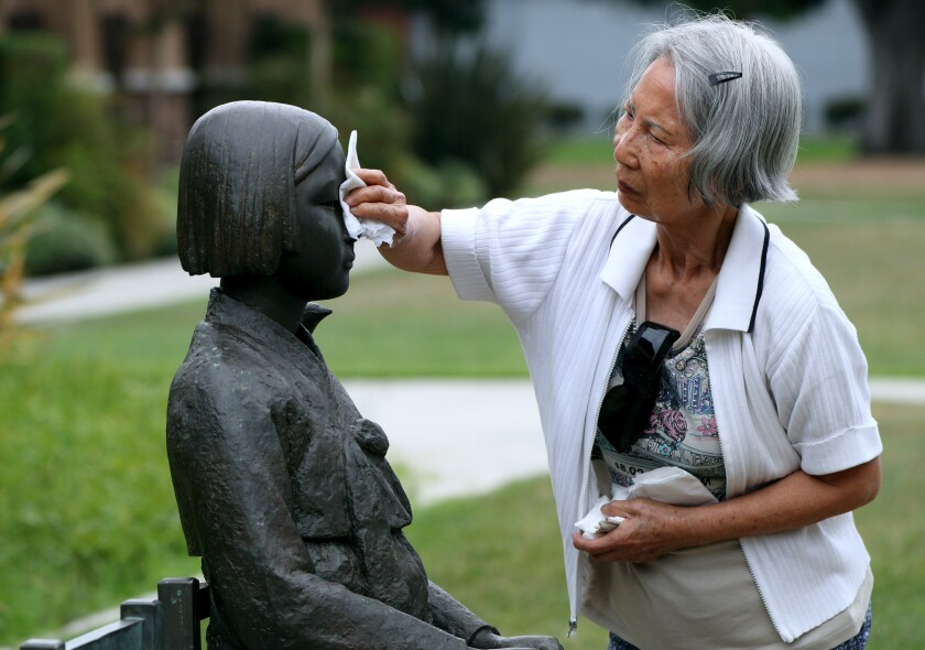 Glendale resident Jean Kuyng Lee, 80, cleans the Korean Comfort Women Peace Monument in Central Park after it was allegedly vandalized with an unknown brown substance on Thursday.