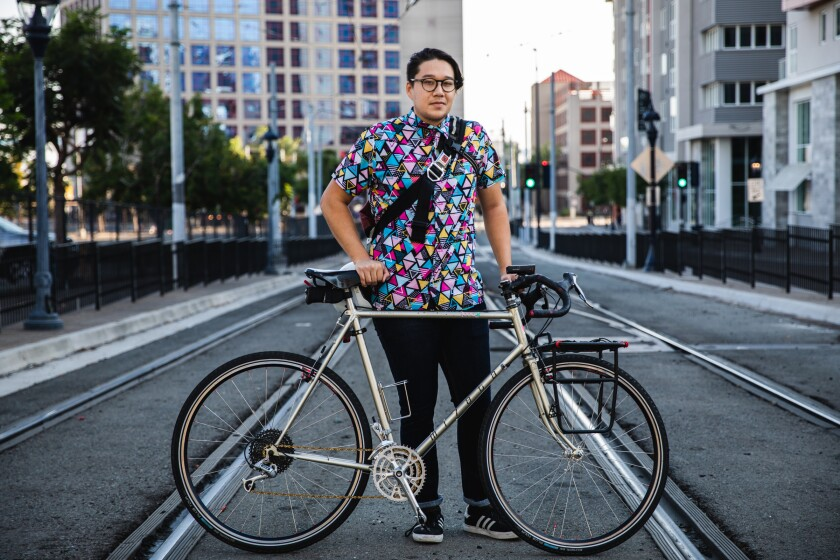 Oliver Zuniga standing on trolley tracks with a bicycle in front of him, looking straight at camera