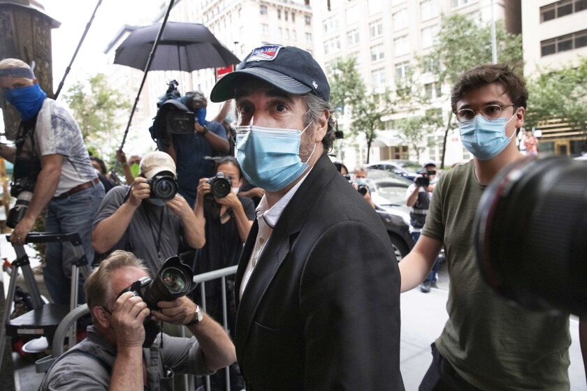 """FILE - This July 24, 2020, file photo shows Michael Cohen, center, President Donald Trump's former personal attorney, returning to his apartment, in New York, after being released from prison. So-called Son of Sam laws won't keep Cohen from profiting from any part of his book, """"Disloyal: The True Story of the Former Personal Attorney to President Donald J. Trump,"""" legal experts told The Associated Press, even if his memoir amounted to a how-to manual for tax evasion and campaign finance violations. (AP Photo/Mark Lennihan, File)"""