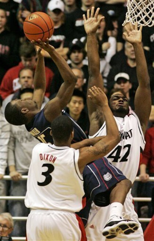 Connecticut guard Kemba Walker (15) shoots between Cincinnati guard Dion Dixon (3) and forward Steve Toyloy (42) in an NCAA college basketball game, Saturday, Jan. 10, 2009, in Cincinnati. Connecticut won the game 81-72. (AP Photo/Al Behrman)