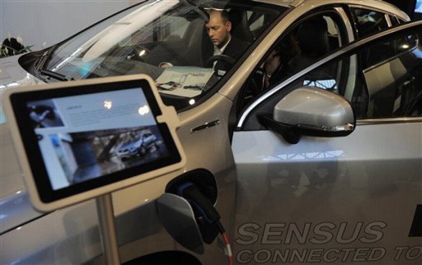 In this Feb. 26, 2013, photo man is pictured inside of a Car Volvo V60 P-IH at the Mobile World Congress, the world's largest mobile phone trade show, in Barcelona, Spain. The first wave of the wireless revolution was getting people to talk to each other through cellphones. The second, it seems, wi